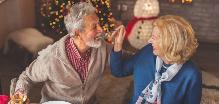 Dania na święta - starsza para jedząca posiłek przy świątecznym stole.